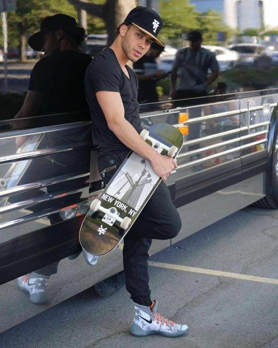 hombre con patineta recargado a lado de camion