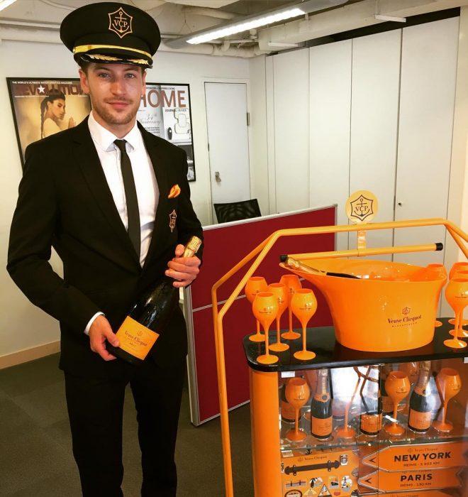 hombre vestido de piloto con botella de champaña y copas