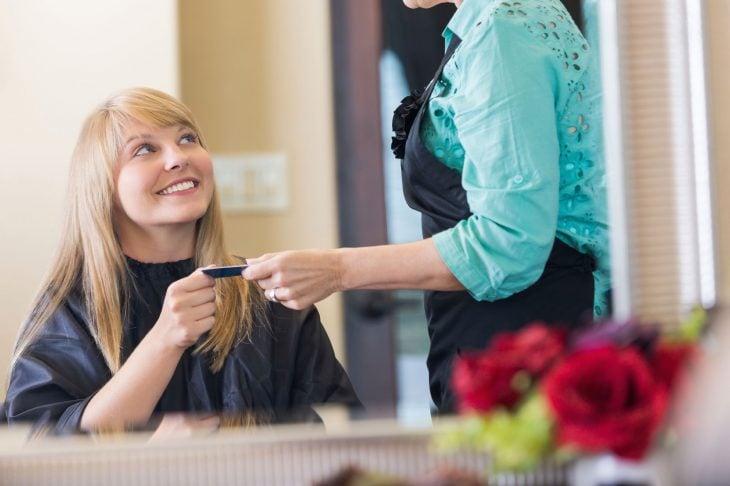 mujer rubia dando su tarjeta a mujer de camisa azul