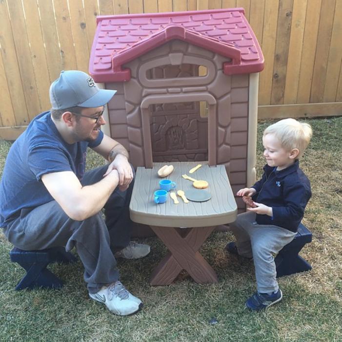 hombre con gorra sentado en mesa con niño