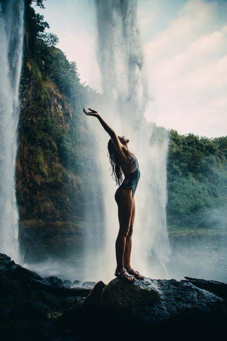 Chica levantando los brazos mientras está frente a una cascada