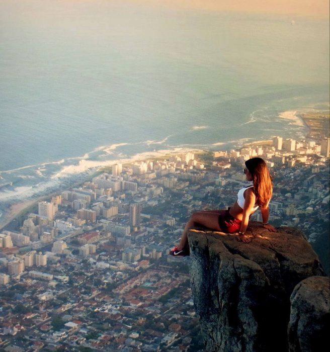 Chica sentada sobre una roca admirando una ciudad