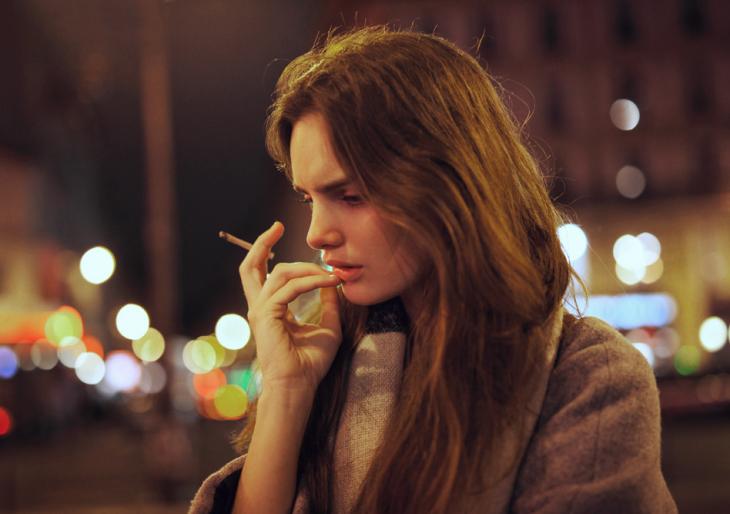 Chica fumando mientras está parada en medio de la calle fumando