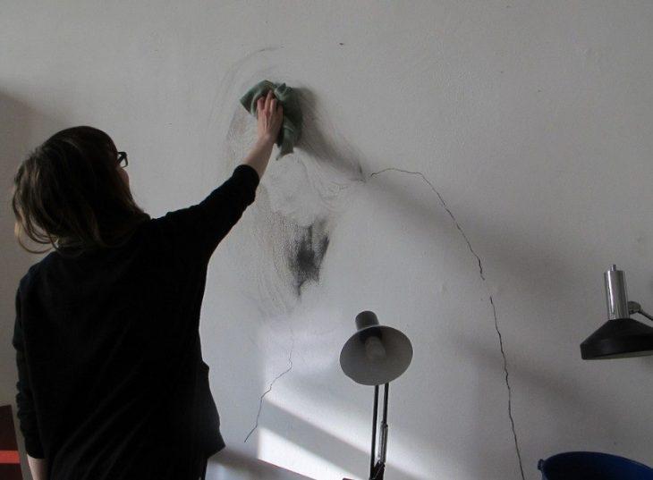 Chica limpiando una pared con un dibujo