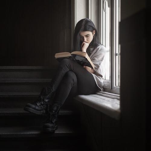 Chica sentada sobre una ventana leyendo un libro