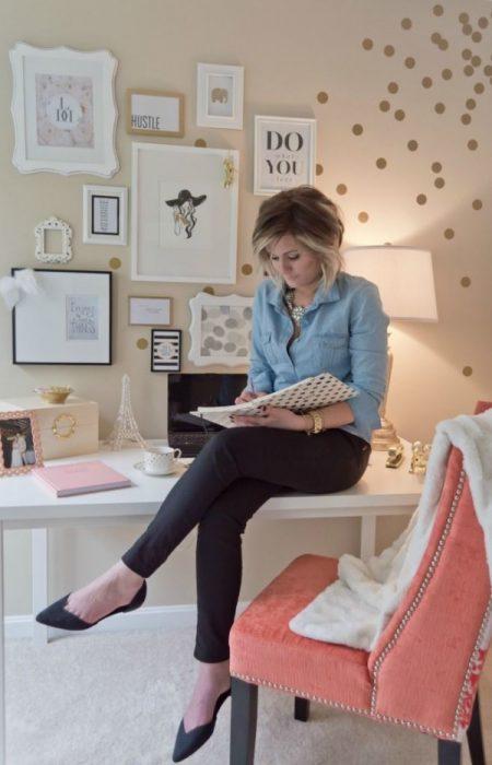 Chica en una oficina sentada en su escritorio mientras escribe en su agenda