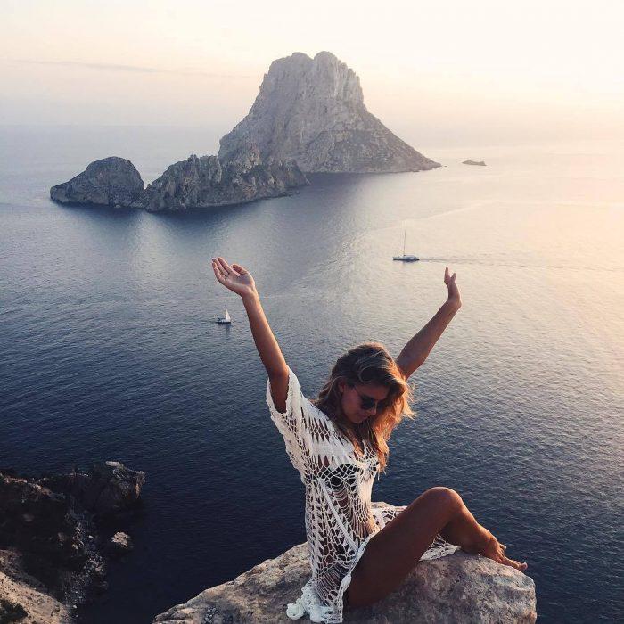 Chica con los brazos levantados mientras está sentada en una piedra admirando el océano