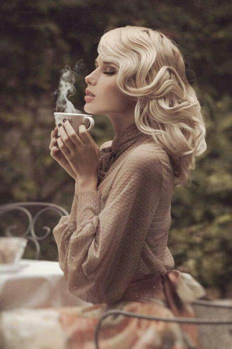 Chica sentada en un jardín inhalando el vapor de una taza de té