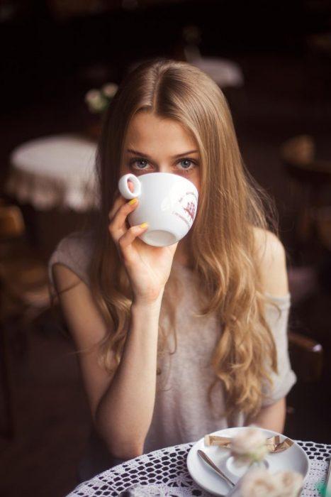Chica sentada en una mesa bebiendo de una taza