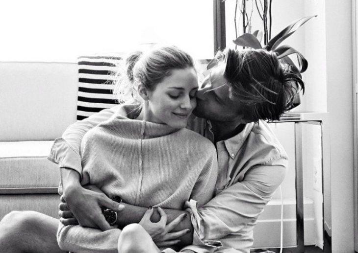 Chico besando a una chica en la mejilla mientras están sentados en el suelo