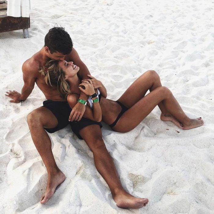 Pareja de novios recostados en la arena de la playa besándose
