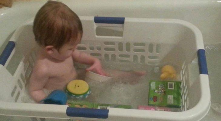 Niño dentro de una caja de pastico que está adentro de una bañera