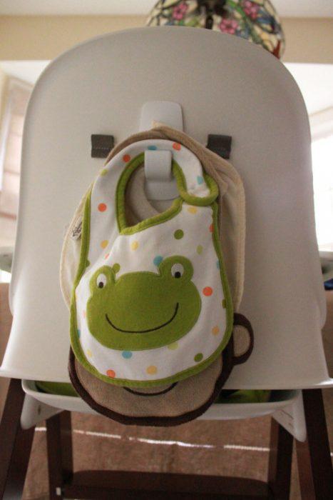Gancho colocado atrás de la silla del bebé para colgar baberos