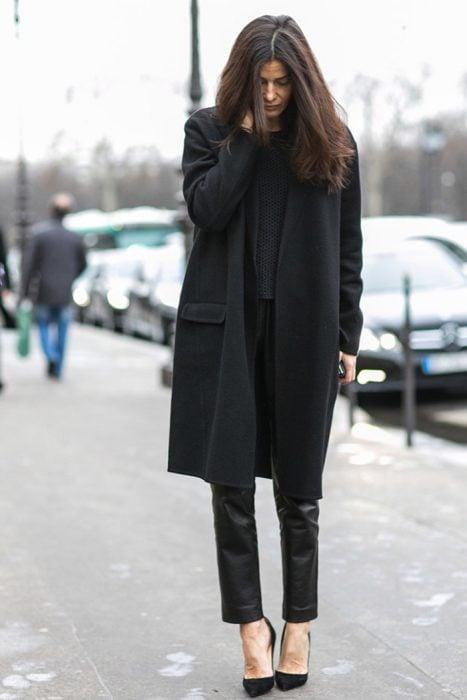 chica vestida de negro con abrigo y zapatos altos