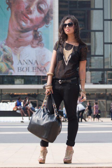 chica con blusa encaje negro, collar dorado y zapatos altos beige
