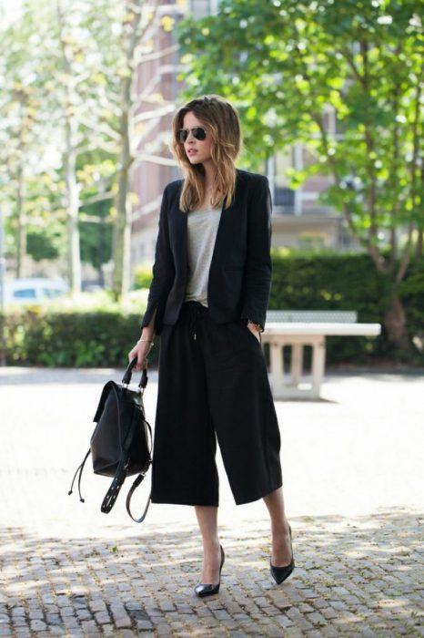 chica con falda pantalón negro y zapatos altos