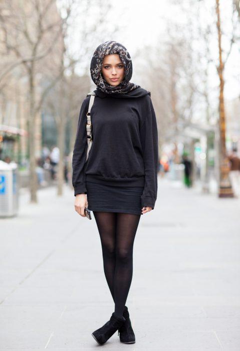 chica con sudadera, falda corta negra y pañoleta