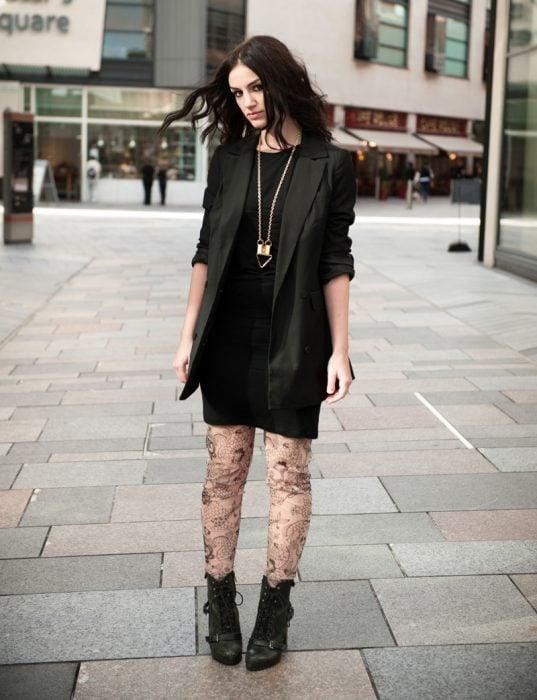 chica con vestido y saco negros, medias de encaje