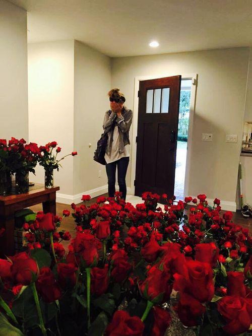 mujer llega a casa con flores
