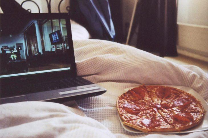 pizza y computadora en cama