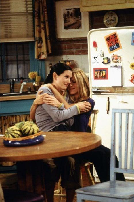 Chicas abrazándose mientras están en la cocina