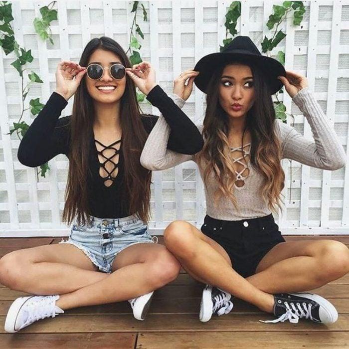 Chicas sentadas sobre un piso de madera usando la misma vestimenta