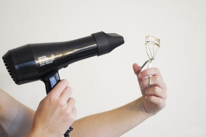 persona aplicando aire de secadora a rizador de pestañas