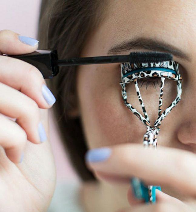 mujer maquillando pestañas sobre rizador
