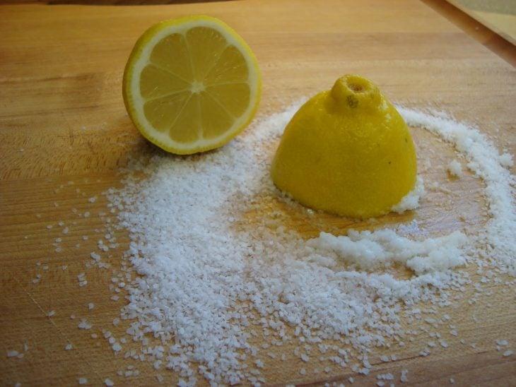 Tabla de madera con carbonato y limón para limpiarla