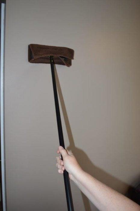 Limpiador de goma con una toalla para limpiar una pared