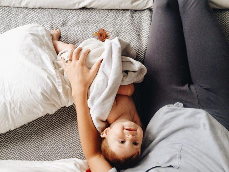 chica con bebé en cama
