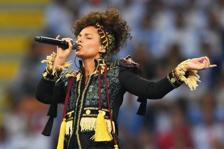 Mujer de cabello rizado con micrófono en estadio