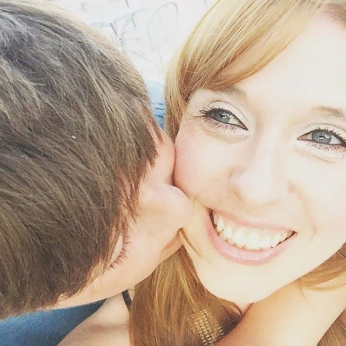 mujer rubia con su hijo mientras la besa en la mejilla