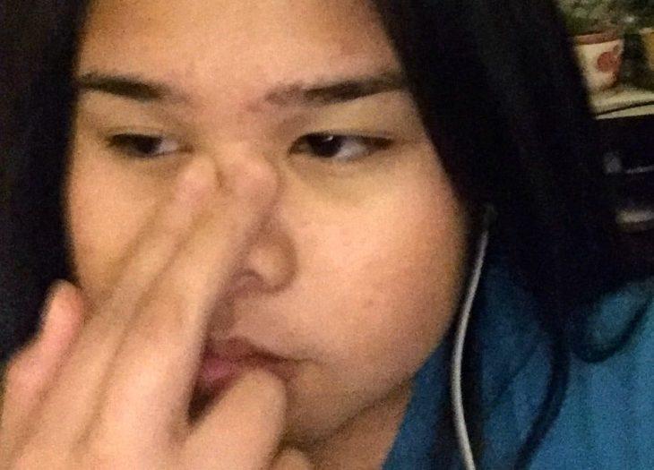 chica con los dedos encima de la nariz