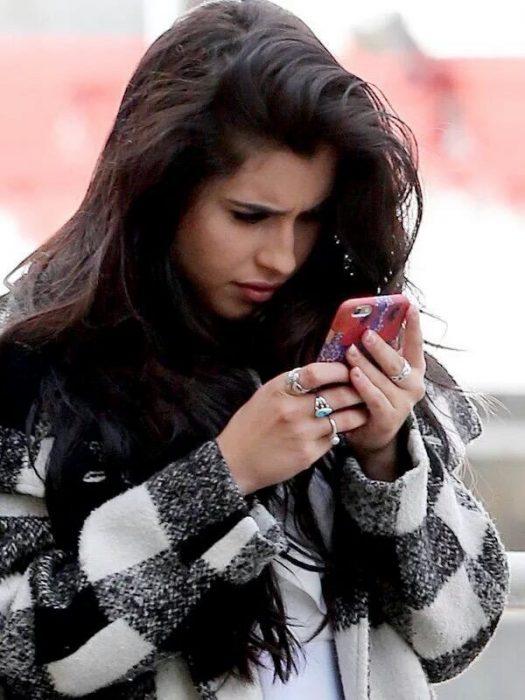 chica tratando de ver celular