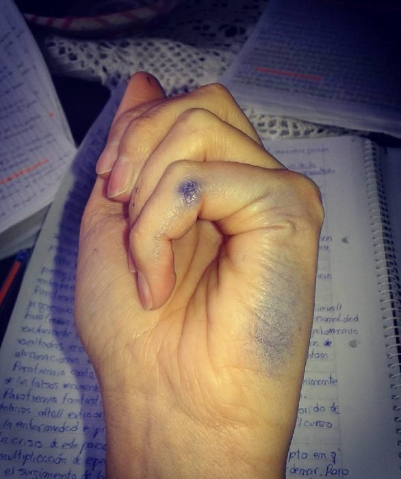 mujer con mano izquierda manchada de tinta