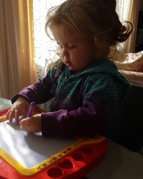 niña pequeña dibujando con mano izquierda