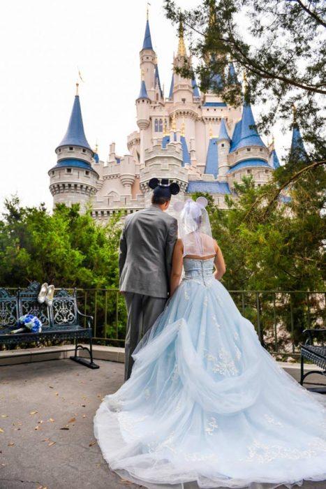 Pareja de novios dando la espalda viendo el castillo de Disney