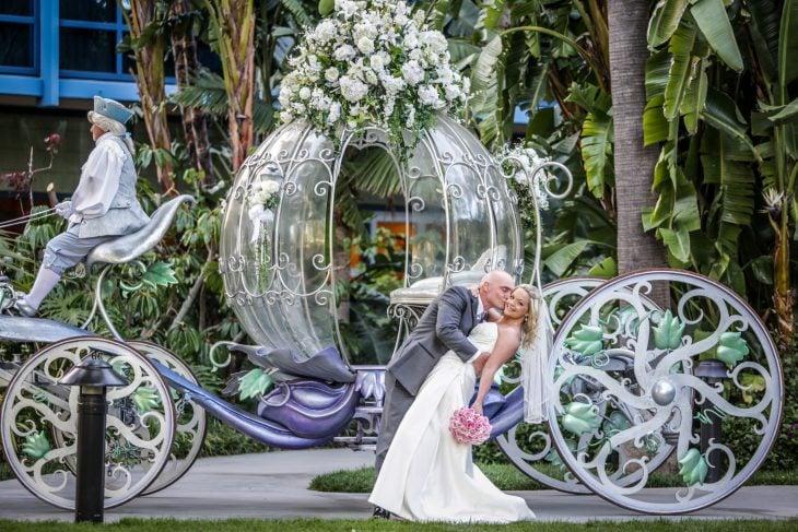 Pareja de novios frente una calabaza de cristal el día de su boda