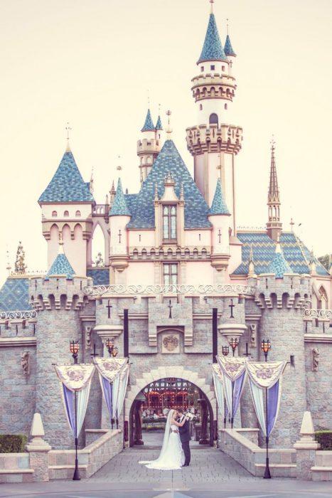 Pareja de novios besándose frente al castillo de Disney