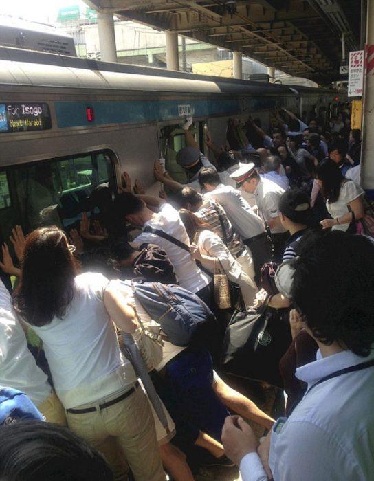 multitud empuja un vagón del metro
