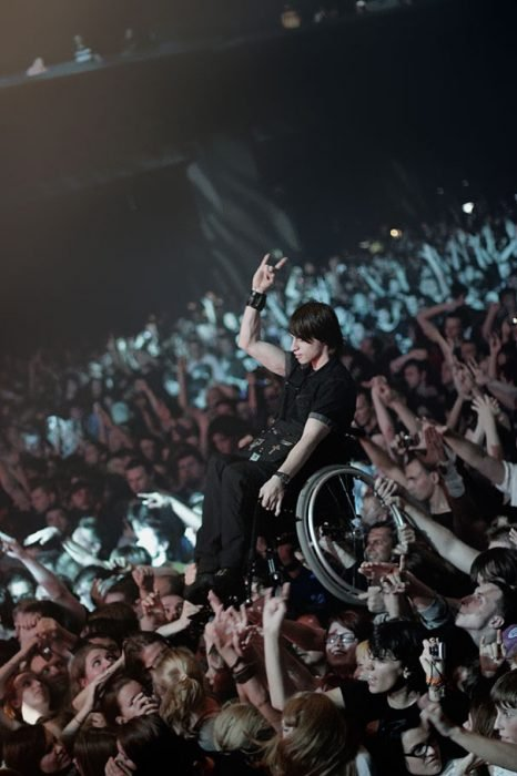 chico en silla de ruedas levantado por la multitud en concierto