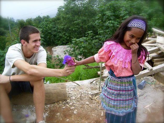 turista regala una flor a una niña guatemalteca