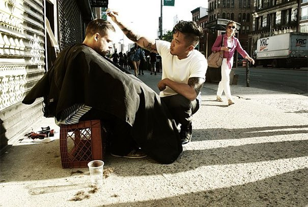 chico cortando el cabello a persona de la calle