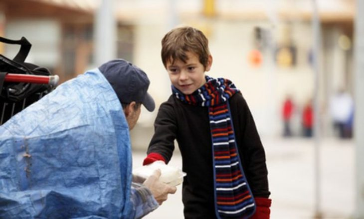 niño da comida a un hombre sin hogar