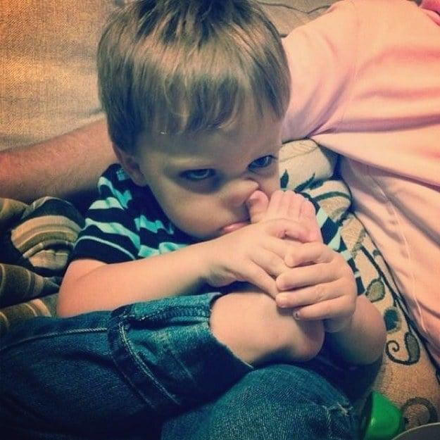 niño picándose nariz con dedo del pie