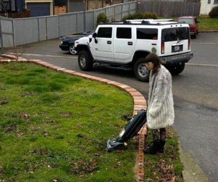 mujer tratando de aspirar césped
