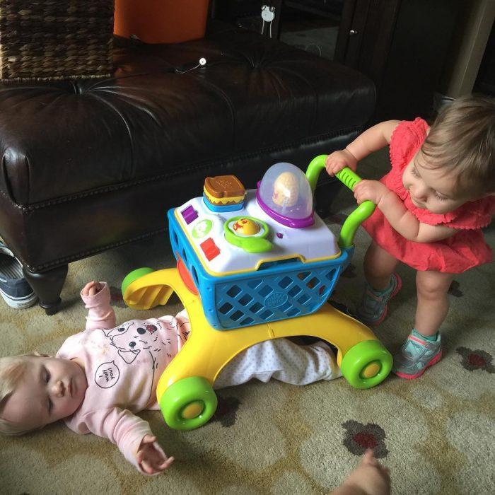 niñas pequeñas jugando con carrito