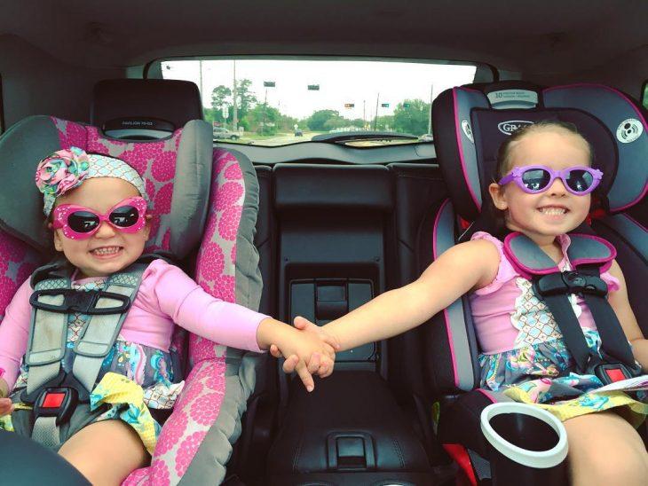 niñas con lentes tomadas de la mano sonriendo