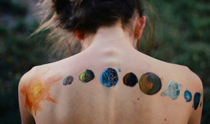 espalda desnuda de mujer con pintura de sol y planetas